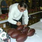Joe Namath signing footballs for National Sports Distributors