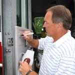 Dwight Clark autographing a fire truck at National Sports Distributors