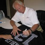 Ken Stabler autographing Raider jerseys for National Sports Distributors