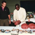 Emmitt Smith autographs footballs for National Sports Distributors