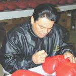 Roberto Duran autographing boxing gloves for National Sports Distributors