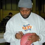 Ron Dayne autographing footballs for National Sports Distributors