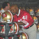 Ronnie Lott autographing helmets for National Sports Distributors