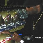 Deion Sanders autographing helmets for National Sports Distributors