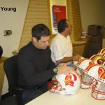 Steve Young autographing helmets for National Sports Distributors